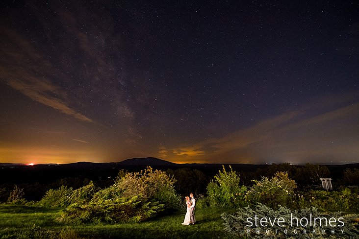 79_Bride and groom hold each other under star lit sky with mountains in background.jpg