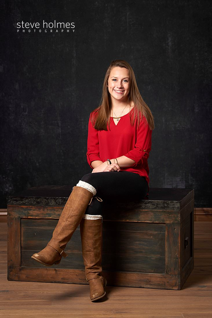 02_Teen girl wearing red blouse and boots sits on a box in studio portrait.jpg