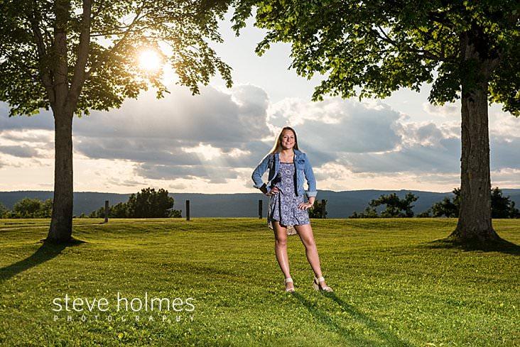 08_Teen wearing jean jacket and dress stands between two summer trees overlooking mountain ridge.jpg