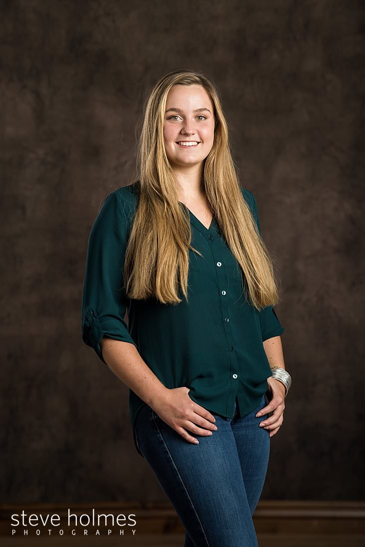 02_Blonde teen in green blouse and jeans stands for studio portrait with hands in belt loops.jpg