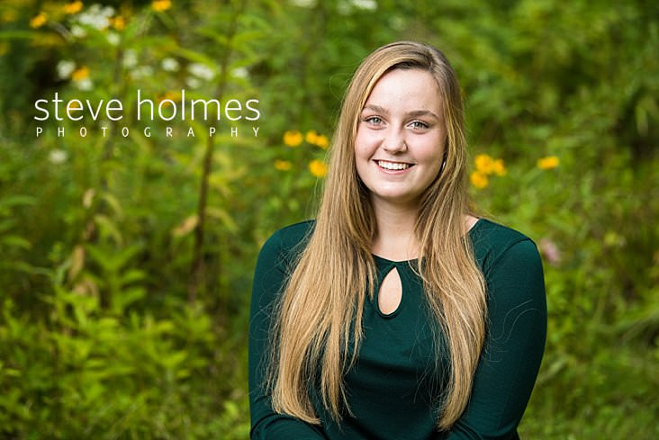 03_Blonde teen in green blouse poses for outdoor senior portrait against summer green backdrop.jpg