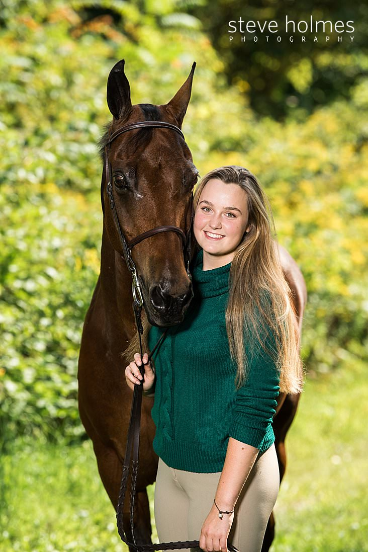 05_Young woman in green sweater stands with her horse outside.jpg