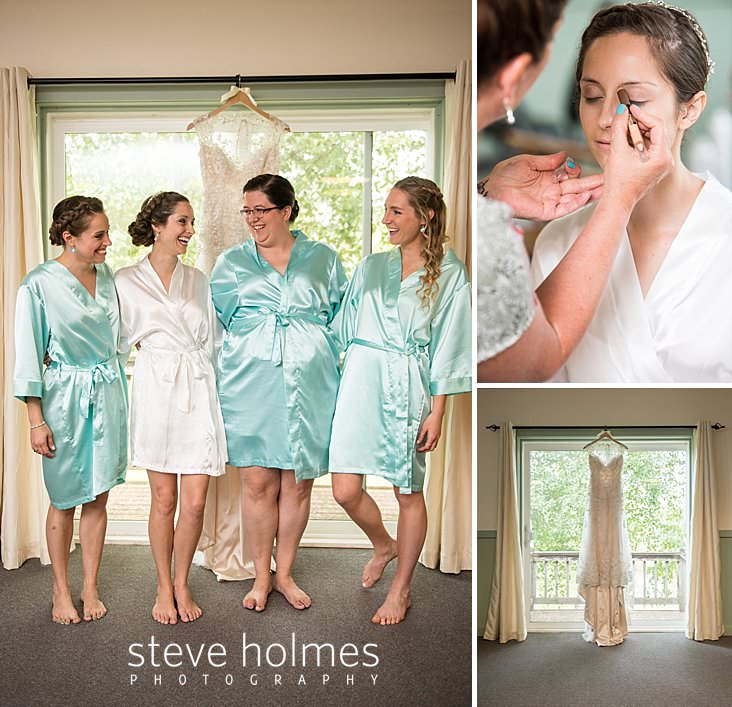 07_Bride laughs with her bridesmaids in their bathrobes with wedding gown hanging in background.jpg