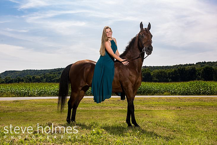 09_Young woman wearing long blue dress poses on her horse in front of a corn field_.jpg