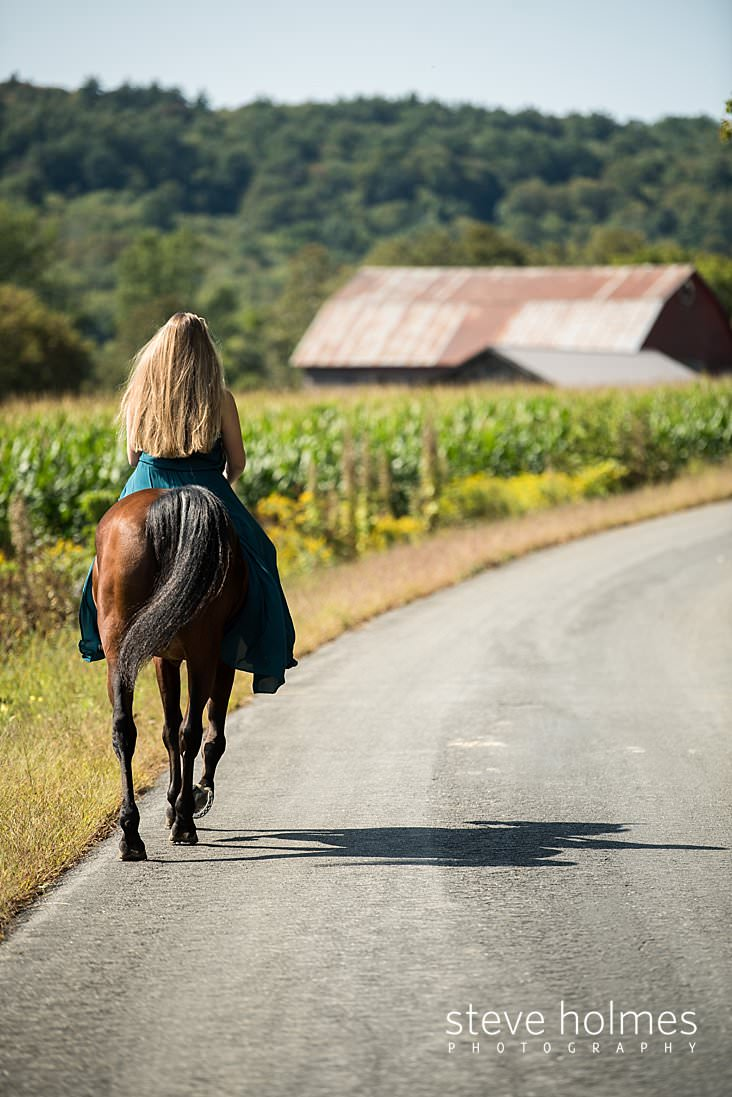 11_Teen girl in long blue dress rides her horse down the road next to a corn field.jpg