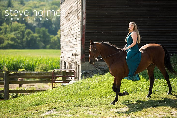 12_Senior portrait of a young woman riding her horse in blue maxi dress next to barn_.jpg
