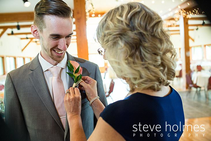 13_Mother of the groom pins on his boutonniere.jpg