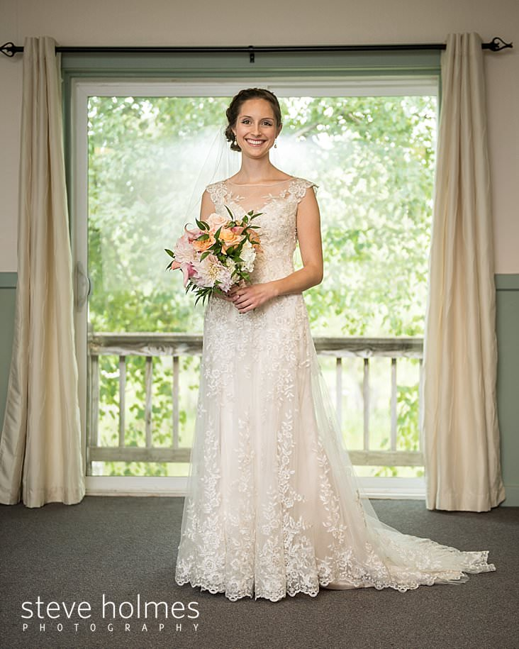 14_Bride stands framed in a window with her bouquet and gown.jpg