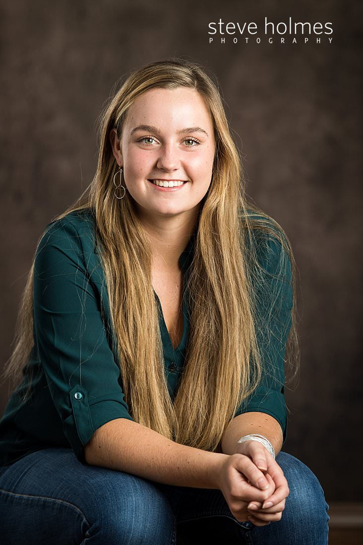 15_Blonde teen girl in green blouse and jeans sits for studio senior portrait.jpg