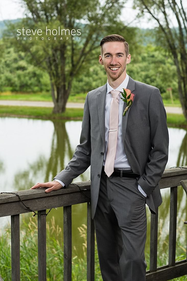 15_Groom in grey suit and pale pink tie stands on a porch overlooking a pond.jpg