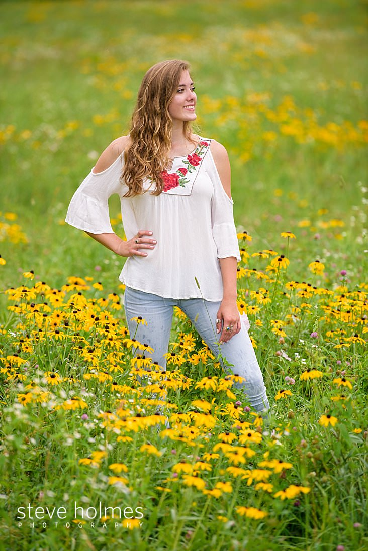 15_Young woman in white blouse stands in a field of wildflowers with her hands on her hip.jpg