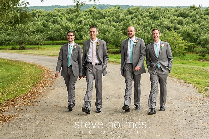 18_Groom walks with his groomsmen on a dirt road through an orchard.jpg
