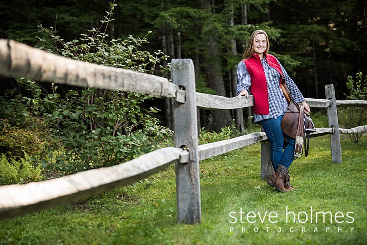 28_Blonde teen wearing red vest leans against wooden fence holding saddle.jpg