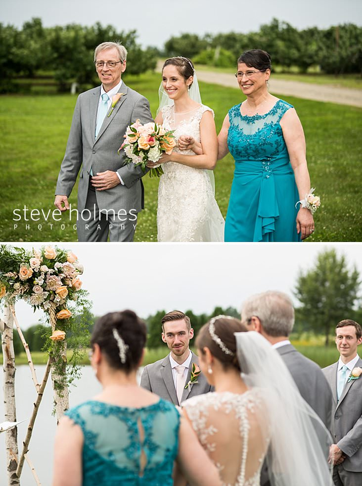 34_Bride is walked down outdoor orchard isle with her parents linked on her arms.jpg