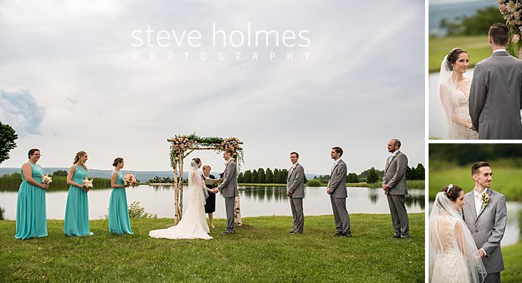36_Bride and groom and bridal party stand under birch altar on the banks of a pond overlooking mountains.jpg