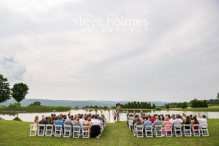 37_Wedding ceremony takes place on the banks of a pond overlooking mountain range.jpg