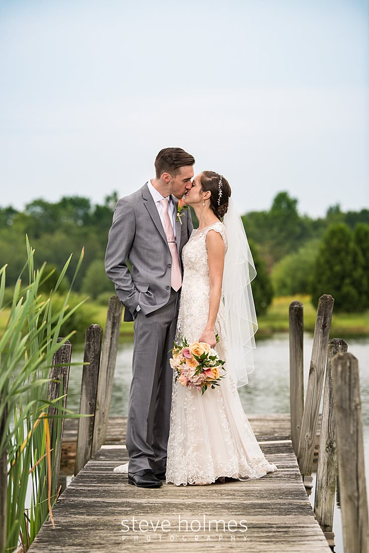 65_Groom leans in to kiss his new bride on the dock of a summer pond.jpg