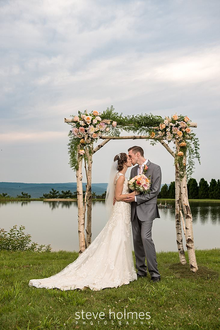 67_Bride and groom kiss alone under their birch altar on the banks of a pond.jpg