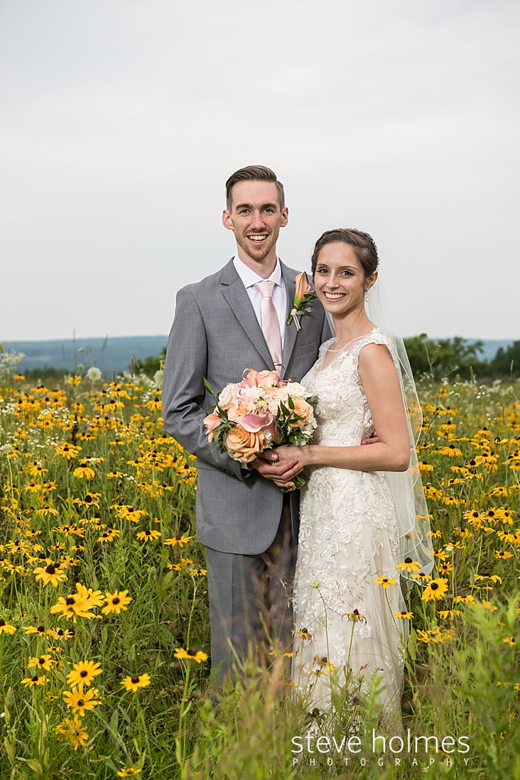 68_Bride and groom pose for portrait in a field of wildflowers.jpg