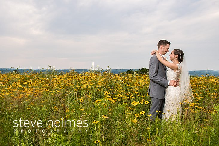 69_Bride and groom wrap their arms around eachother in a field full of wildflowers.jpg