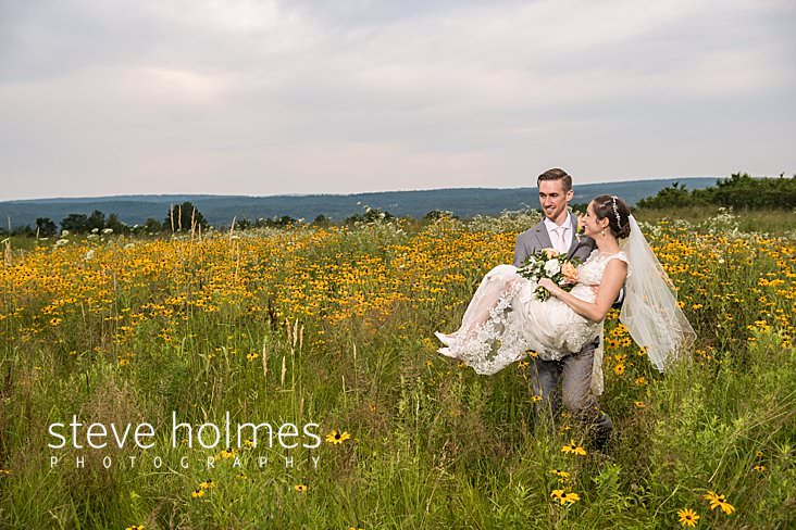 70_Groom carries bride through a field of wildflowers.jpg
