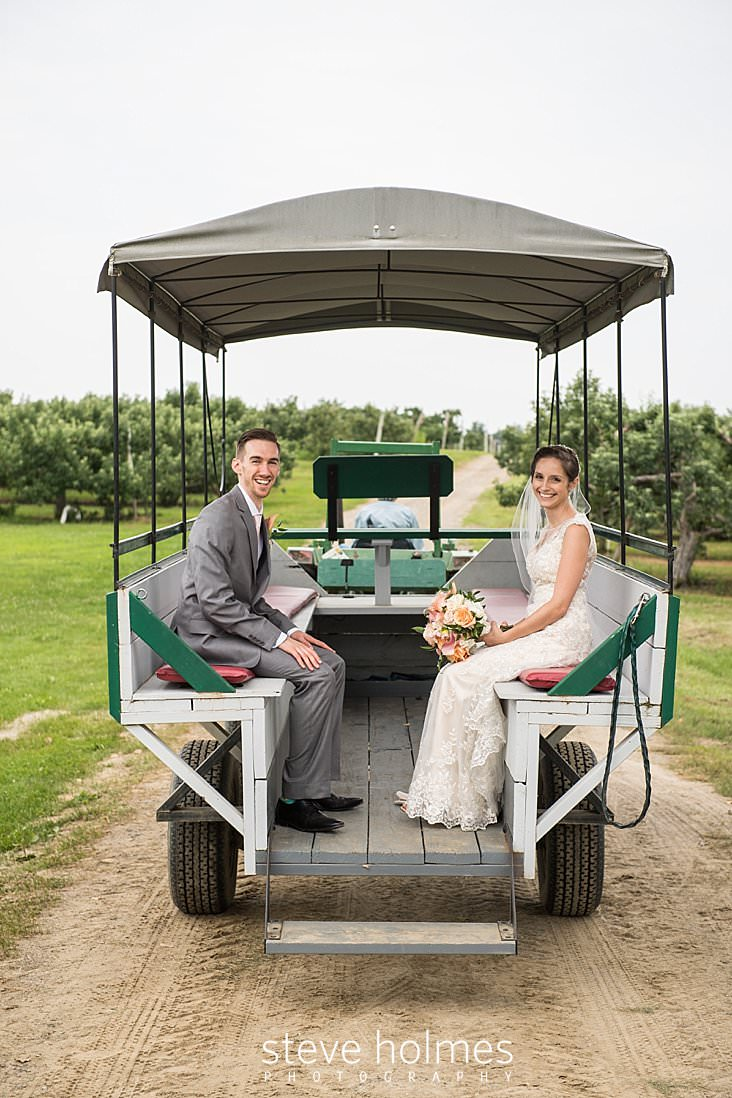 71_Bride and groom ride together to reception in a wagon pulled through an orchard.jpg