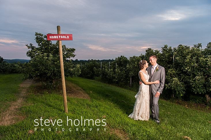 86_Bride and groom stand in an orchard on a summer evening.jpg