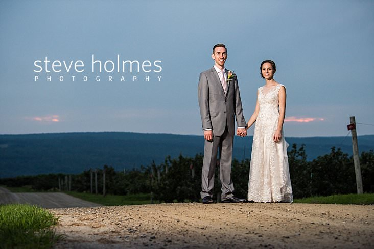 88_Bride and groom stand on a dirt road overlooking an orchard in the evening.jpg