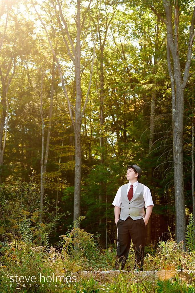 Teen boy wearing hat, vest and tie poses at the edge of a forest