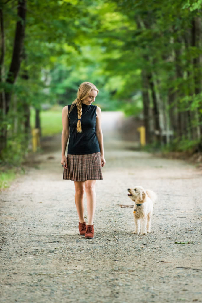 Teen in plaid skirt and blue turtleneck walks down country road