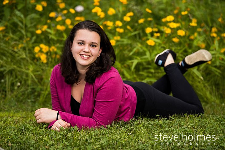 Teenaged girl lays in grass with flowers in background
