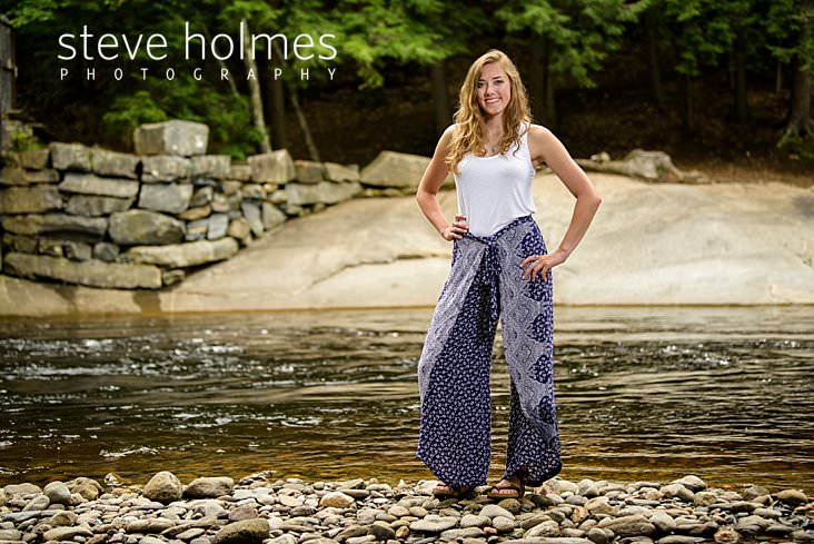 Teenaged girl wearing flowing blue pants stands on the banks of a river