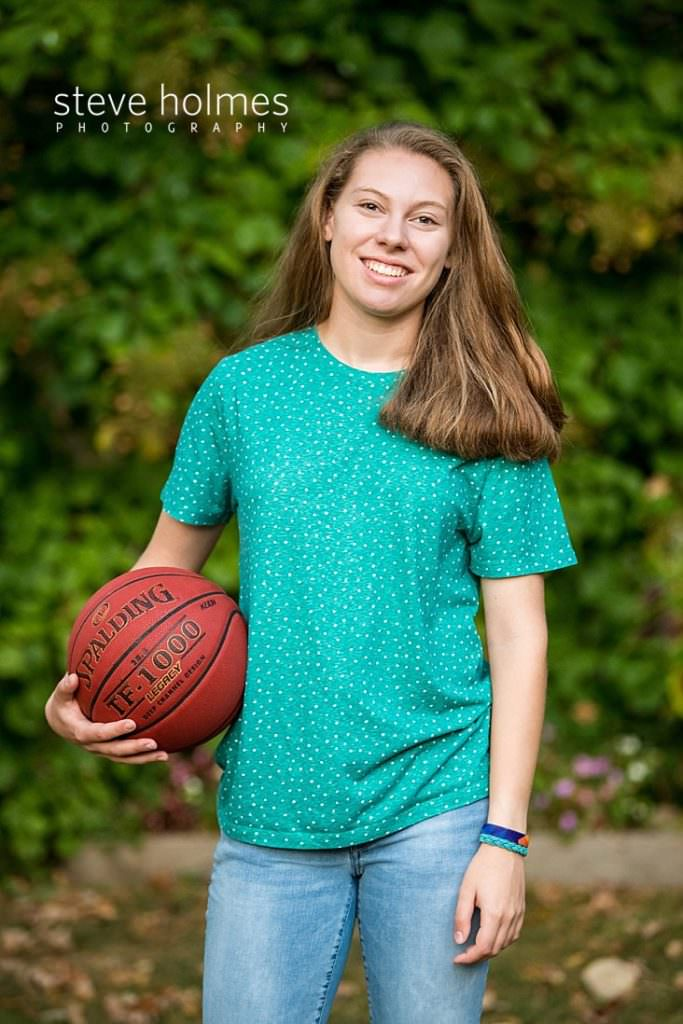 Teen girl poses for outdoor senior portrait with basketball