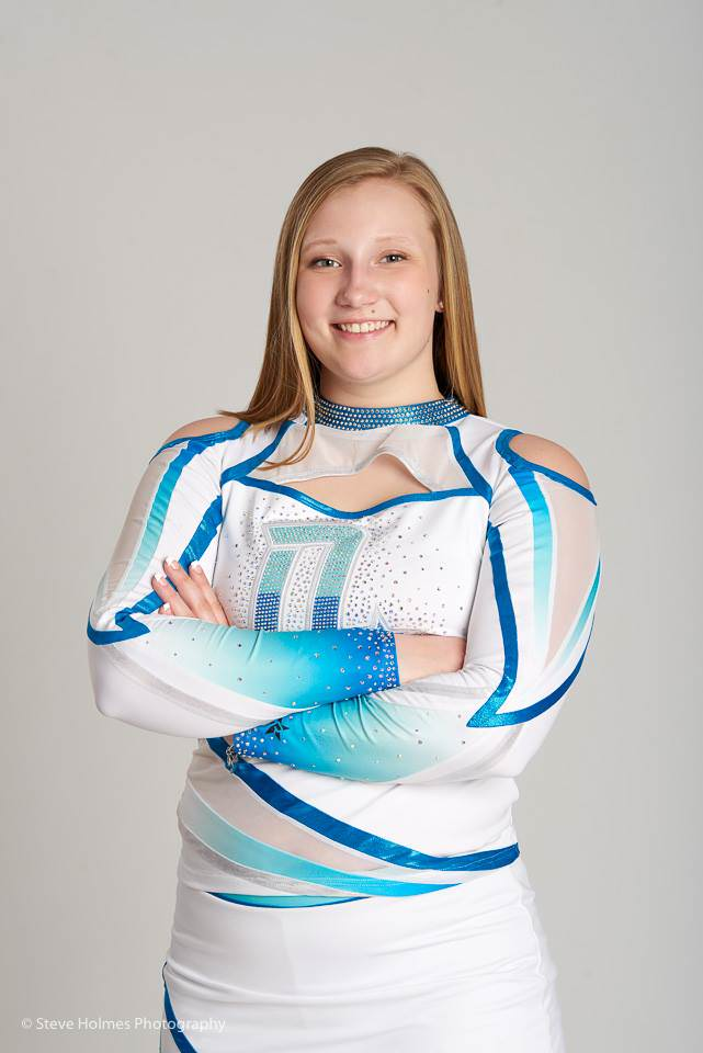 Blonde teen in cheerleading outfit stands for studio portrait
