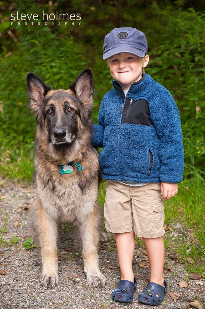 Little boy stands next to German Shepherd