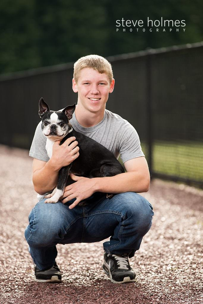 Teen boy poses with his dog for senior portraits