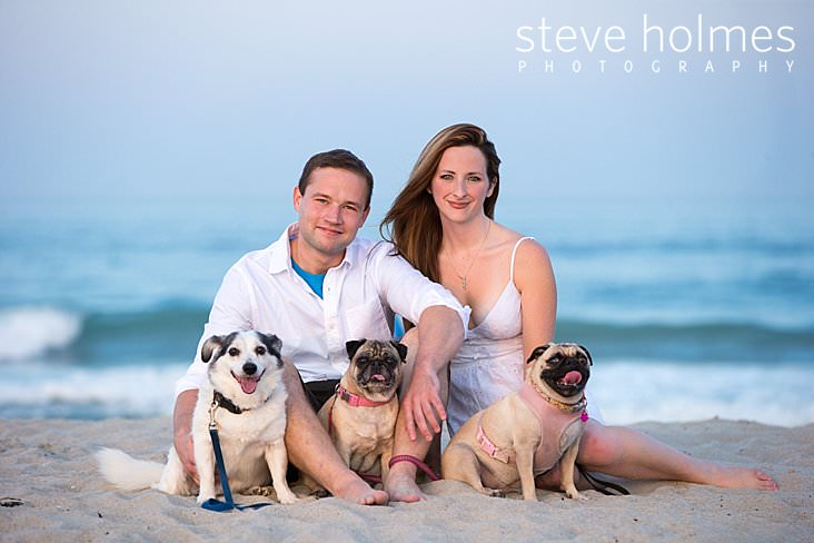 Young couple poses on the beach with their three dogs