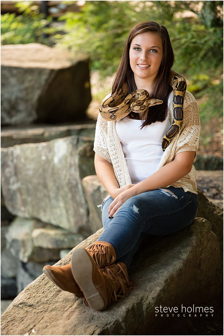 brunette teen poses with snake for senior portrait