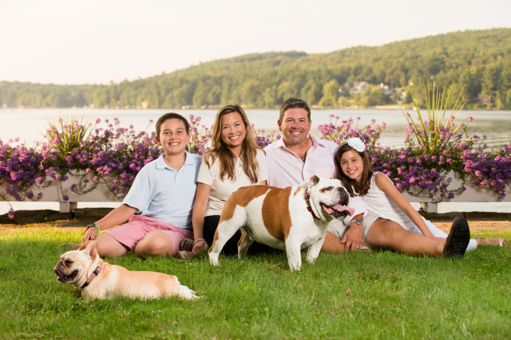 Family of four pose with dog next to lake