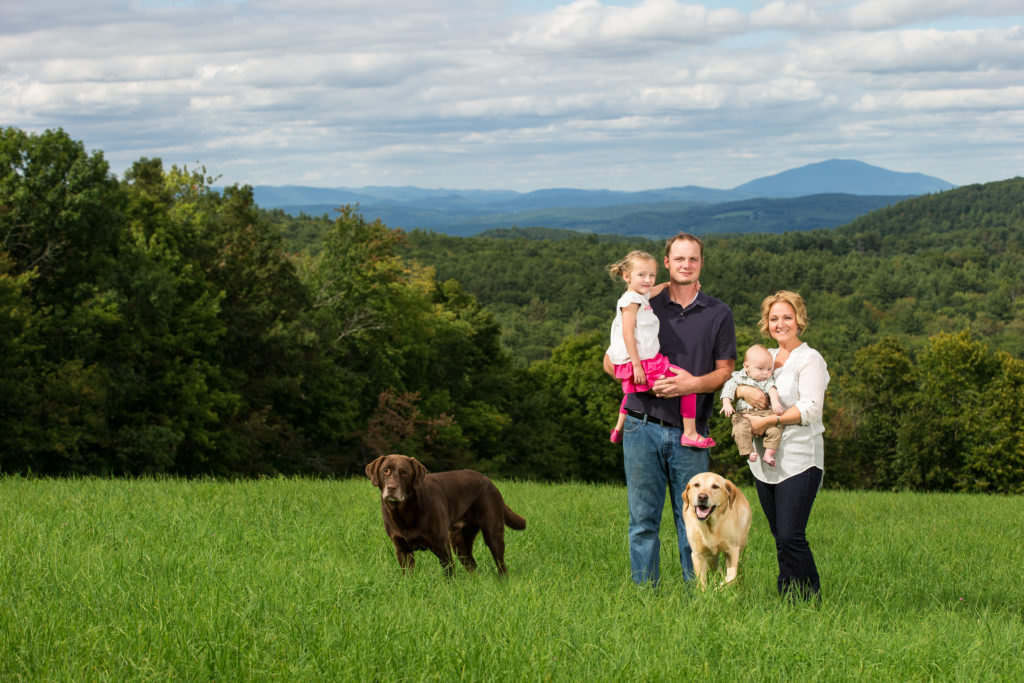 Family with young children pose in field with two dogs