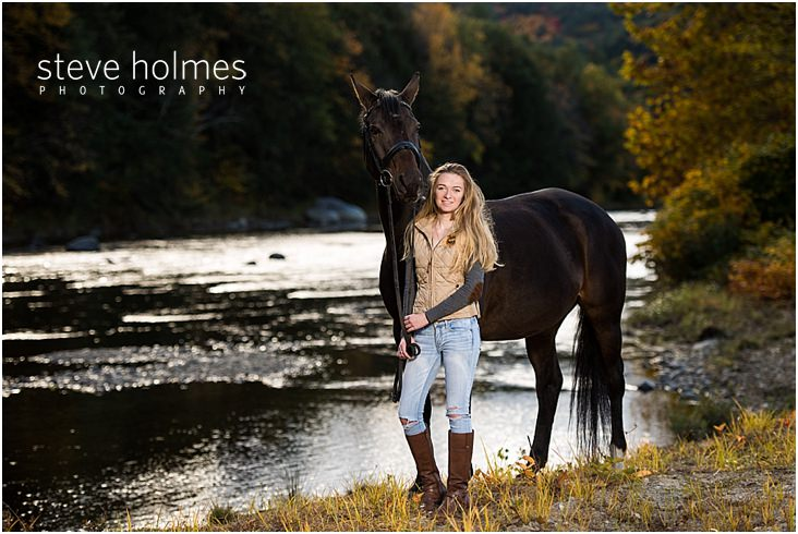 Young woman stands with her horse on the riverbank