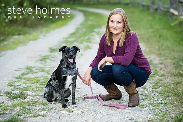 Young woman poses for senior portrait with her dog on a country road