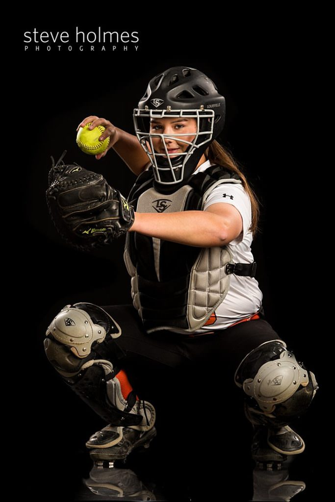 Young woman poses in her catcher softball gear