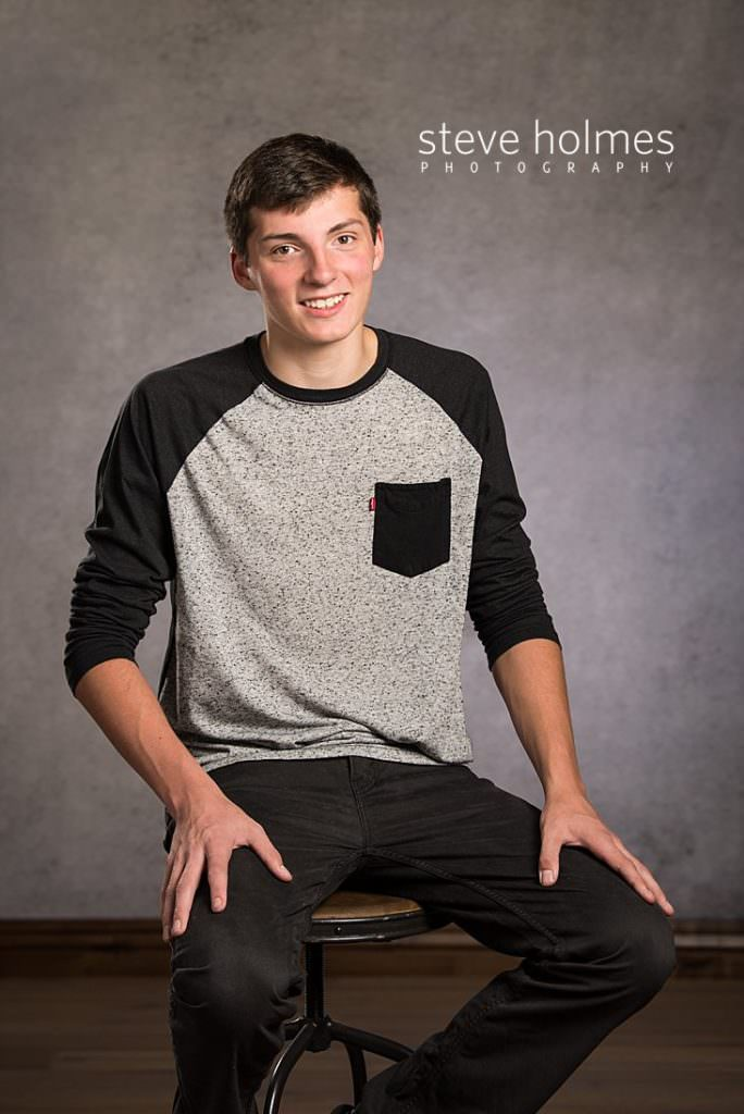 Young man sits on stool for studio senior portrait
