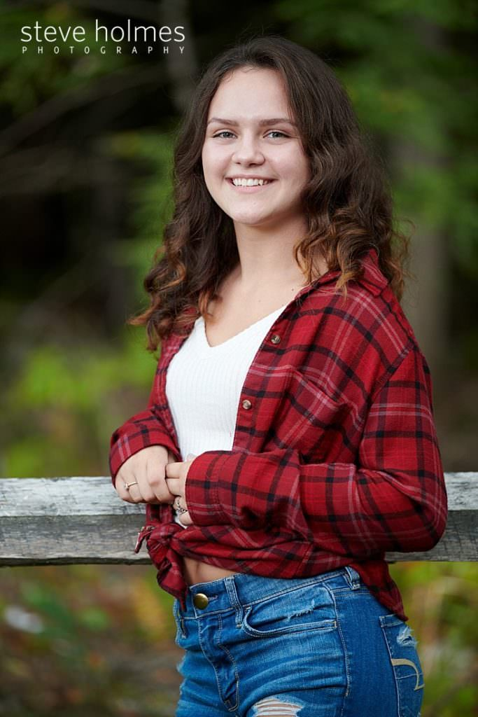 Teen in flannel shirt leans against wooden fence