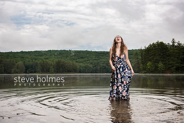 Teen girl wearing dress laughs while standing in lake