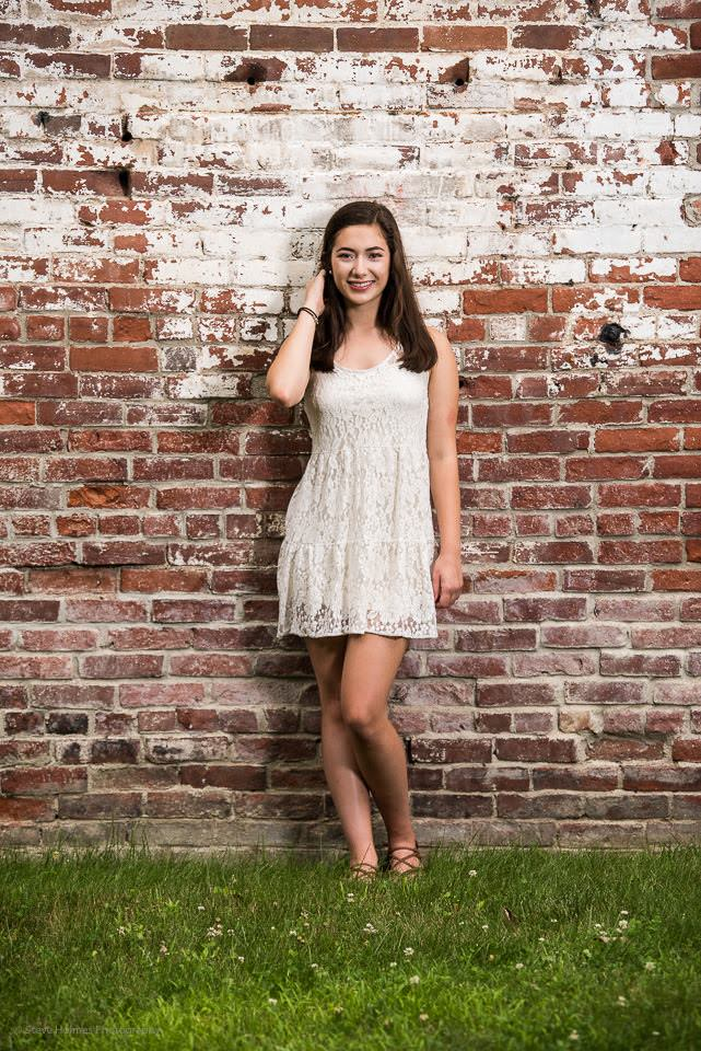 Young teen girl poses in front of a brick wall for senior portrait