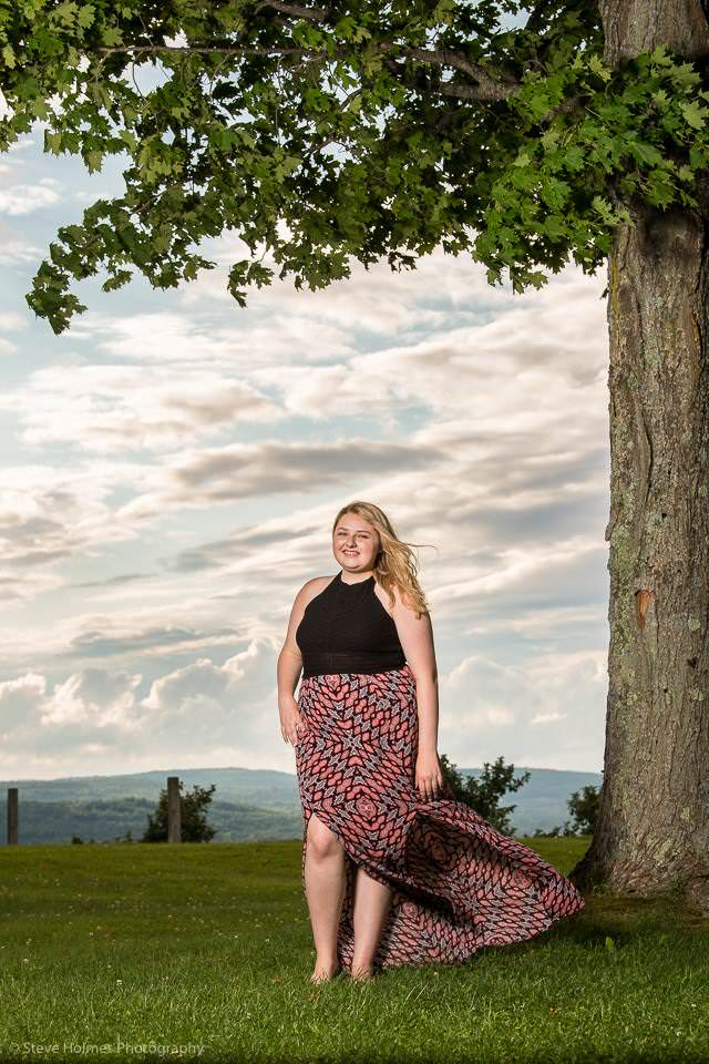 Young woman poses for senior portrait under tree