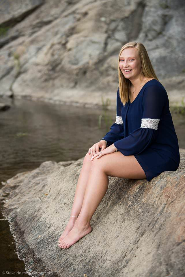 Young blonde woman sits on rock in river for portrait