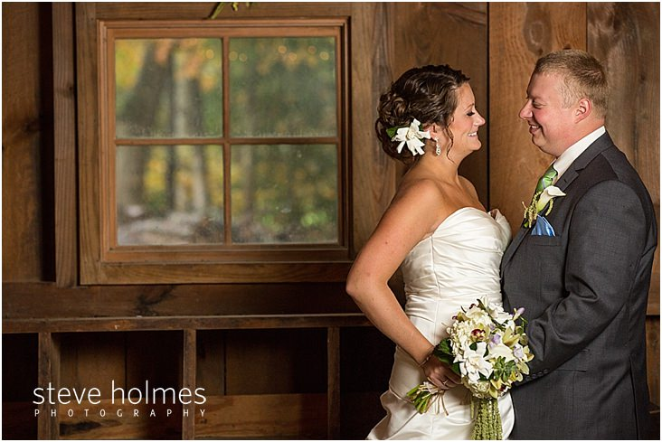 24_bride-groom-smile-at-each-other-by-barn-window